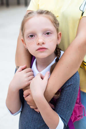 red-haired girl, schoolgirl looks sad. freckles and orange braids. mom hugs the girl. back to school
