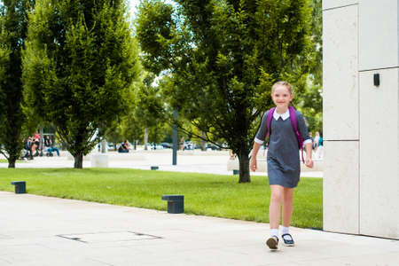 cute redhead schoolgirl laughs, goes to school with a knapsack. happy back to school. Stockfoto