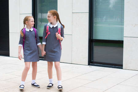 two cute redhead schoolgirls go to school. laugh and chat. sisters in school uniform. place for text.