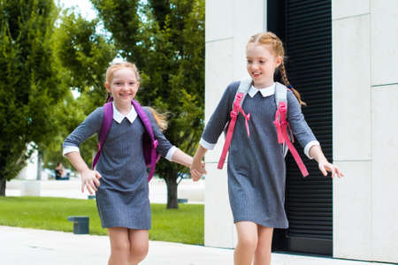 two cute redhead schoolgirls go to school. laugh, chat and run. sisters in school uniform Stockfoto
