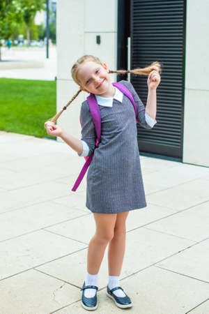 cute redhead schoolgirl laughs, holds herself by her pigtails. happy back to school.