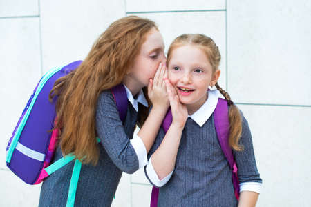 two redhead schoolgirls gossip. she put her hand to her ear and whispers secrets