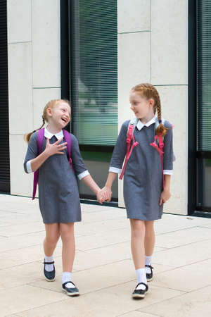 two cute redhead schoolgirls go to school. laugh and chat. sisters in school uniform.