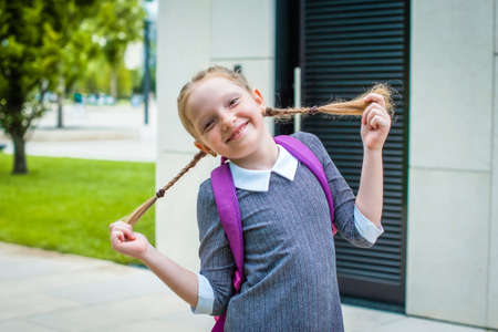 cute redhead schoolgirl laughs, holds herself by her pigtails. happy back to school