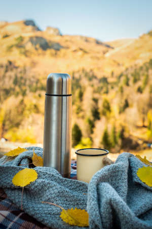 picnic, autumn forest. against the background of mountains retro , mug and scarf. orange leaves. fall has come