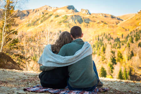 Autumn Walk, mountains. Rear view of couple sits and admires the fall forest. Man and woman in warm clothing and scarf Stockfoto