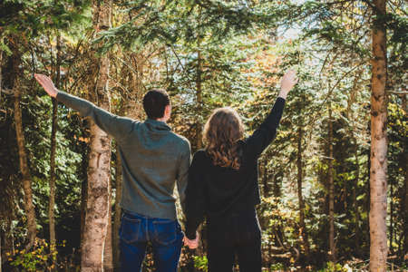 Autumn Walk in the forest. Rear view of couple stands with arms outstretched. Man and woman in warm clothing are happy.