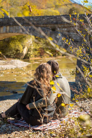 Autumn Walk. Rear view. of couple sits on the river bank. Man and woman in warm clothing looking at a fall view Stockfoto