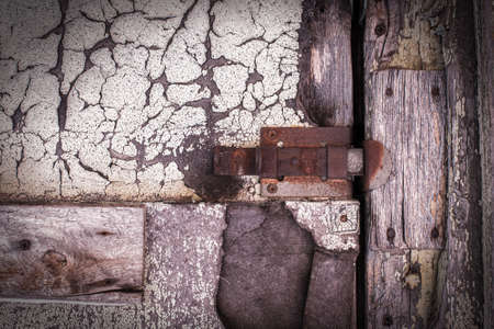 rusty lock on a texture of old, wooden, pink, purple, brown door, which the old paint flaking. the passage is closed. locked. place for text Stockfoto