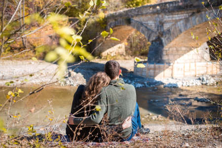 Autumn Walk. Rear view of couple sits on the river bank. Man and woman in warm clothing looking at a fall view