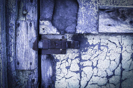 rusty lock on a texture of old, wooden, purple, door, which the old paint flaking Stockfoto