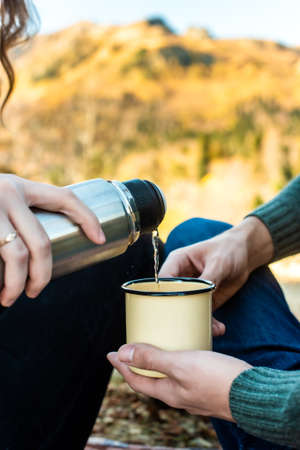 picnic in the autumn forest. female hands pour tea from a into a retro mug. romantic walk fall