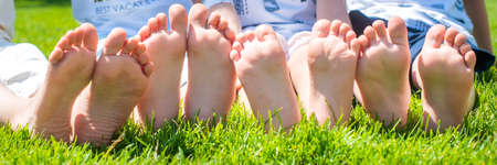 baby bare legs in the frame. barefoot on the grass brother and sister. four. wrinkled. fun together Stockfoto