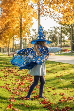 little blonde girl dressed as a witch, wizard for halloween. hat, cloak, pumpkin, laugh, smile, autumn holiday