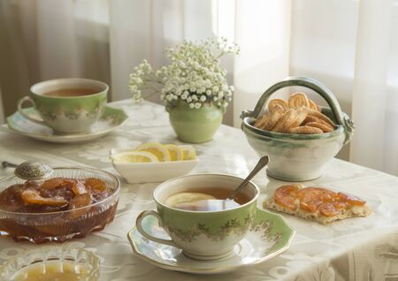 Delicious fresh breakfast for two. Tea with lemon, apple jam and biscuits Banco de Imagens