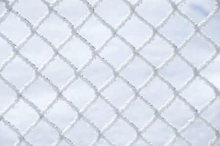 Close up of snow laying on the squares of a wire farm fence with snow in background - Image