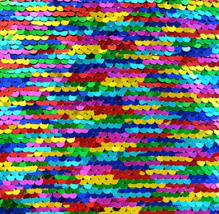 Sequins close-up macro. Abstract background with multicolor sequins on the fabric. Texture scales of round rainbow sequins with color transition.