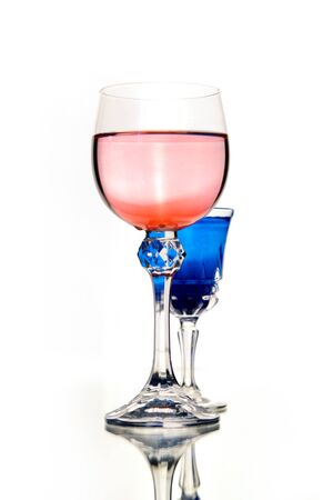 rose wine and blue coctail in beautiful vintage crystal glasses on white wall background, with copy space. Wine list, bar drink menu, wine boutique or degustation, Vertical crop concept