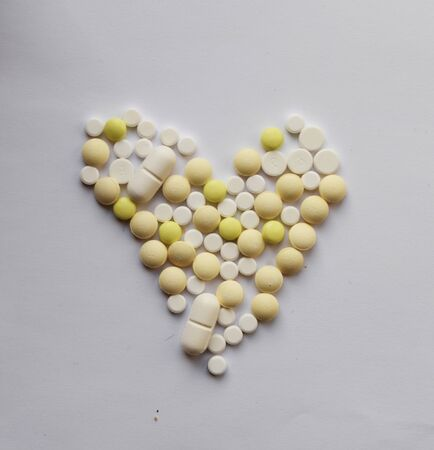 Pharmacology assorted medicine pills, tablets and capsules heart love frame. Different colors tablet on white background. Health care. Top view with Copy space