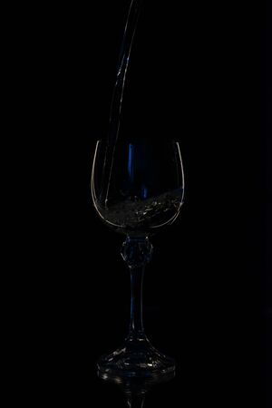 Wine in beautiful vintage crystal glasses on black wall background, with copy space. Wine list, bar drink menu, wine boutique or degustation, square crop concept. Water is poured into a glass