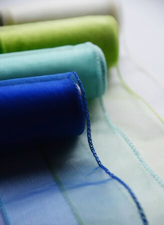 Reels organza ribbon pastel colors white blue green isolated white background. Design concept for Sewing and handcraft subject. Selective focus