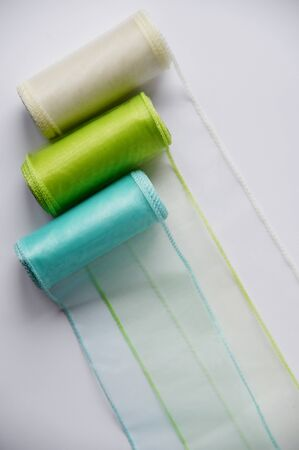 Reels organza ribbon pastel colors white blue green isolated white background. Vertical Design concept for Sewing and handcraft subject. Top view with Copy space