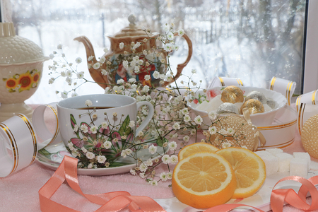 A cup of coffee with lemon and flowers in a festive ribbon, a plate with sweets on a snowy window, 版權商用圖片