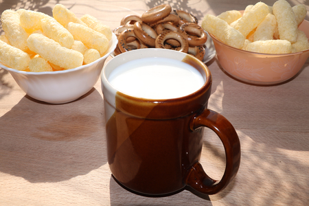 A mug of milk and a cup with popcorn on a sunny table, a bouquet of spring flowers for mood, diet food and a healthy lifestyle in the village, the perfect morning in the village Banco de Imagens