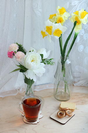 A mug of tea, a cup of corn and a cake on a sunny table, a bouquet of spring flowers for mood, diet food and a healthy lifestyle in the village, a beautiful morning in the village