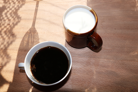 A cup of coffee and a cup of milk on a wooden background, the coziness of a new country house and a sunny bright morning