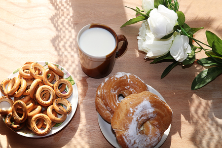 A mug of milk, a cup of corn and cake on a sunny table, a bouquet of spring flowers for mood, diet food and a healthy lifestyle in the village, a perfect morning in the village Banco de Imagens