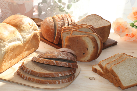 A loaf and slices of fresh bread on a sunny table. Healthy food and healthy ecological product.