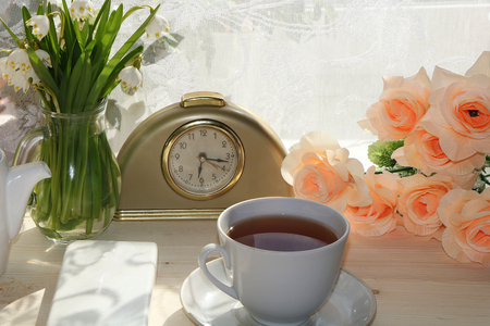 Smartphone, alarm clock and tea on a sunny table. Early morning of a modern person. Fresh flowers in the background for a good mood for the whole working day. 스톡 콘텐츠