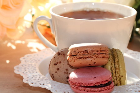 Fresh macaroons with tea on a light background. Extremely shallow depth of field with selective focus in the foreground.
