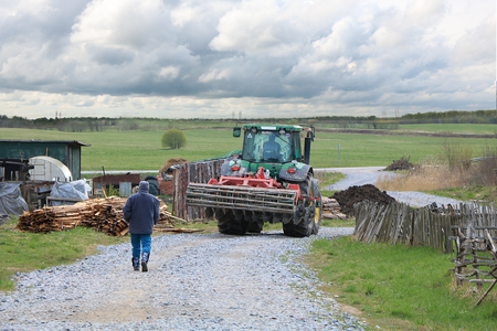 Russia, Leningrad region, 4 May, 2019, Russian village. Russian village in spring and a tractor that prepares for tillage and a tractor driver's assistant, going to the field. Collapsed sheds and devastation, leaning fence.,harsh reality