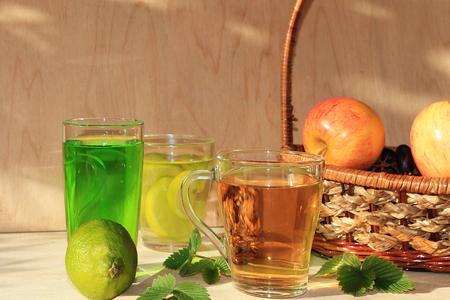 Cal en copas de cristal y fruta con menta en una mesa de madera. Refrescos frescos en un día caluroso, comida dietética en verano.