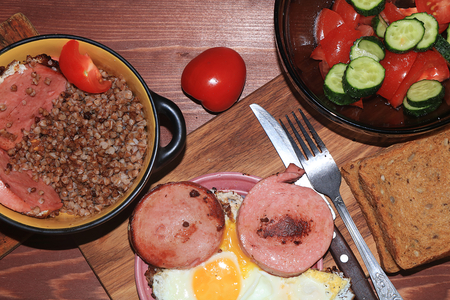 Natural organic buckwheat porridge in a clay pot, scrambled eggs and a salad with tomatoes. Delicious dietary breakfast of cereal and vegetables on a wooden background. Banco de Imagens
