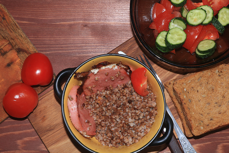 Natural organic buckwheat porridge in a clay pot, scrambled eggs and a salad with tomatoes. Delicious dietary breakfast of cereal and vegetables on a wooden background. Banque d'images