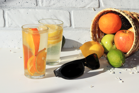 Black sunglasses next to orange and lemon juice, fruit in a basket. Morning refreshments on a hot summer holiday are good for dieting, black glasses for being on the beach Reklamní fotografie