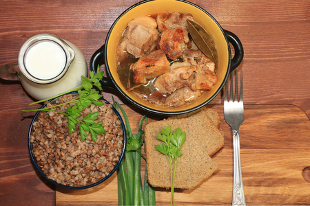 Natural organic buckwheat porridge in a clay pot, meat in a pot, a jug of milk and onions with parsley, top view. Delicious dietary breakfast of cereal and meat on wooden background. Stock Photo