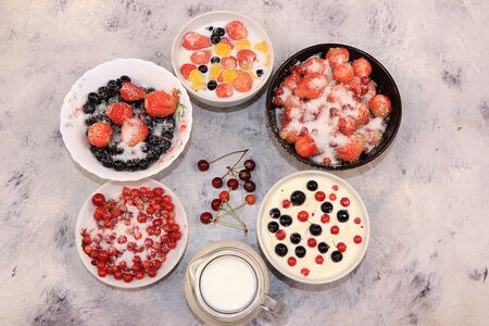 Strawberry yogurt, milk and ripe berries of currants and strawberries on a light background. Delicious healthy breakfast of yogurt and strawberries with copy space, top view, selective focus 스톡 콘텐츠