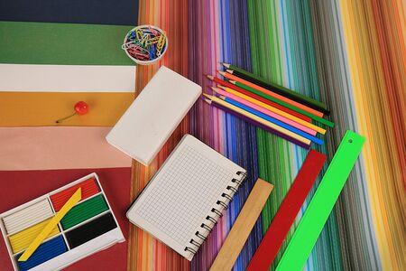 Back to school, Assortment of colored pencils, pens and rulers, on a very bright rainbow abstract background, top view. Bright background and colors form extraordinary thinking and development in children.