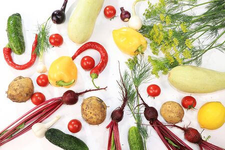 Summer vegetables on white background, top view, copy space. Pepper, dill, tomatoes, onions, beets, cucumbers, zucchini, ingredients for salad, concept of healthy food and diet.