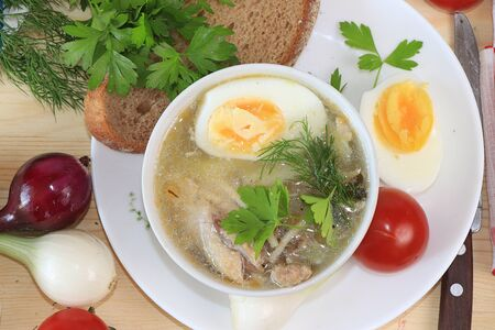 Traditional Russian soup with egg and bread on a wooden table. Delicious traditional natural food and cooking ingredients, healthy diet concept, top view, selective focus.