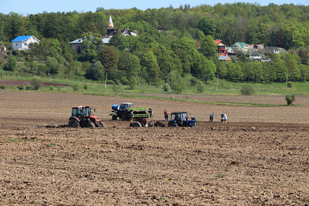 Russia, Leningrad region, May 19, 2019, Russian village. Russian village in the spring, planting cabbage and tractor, which plow the field, workers who watch the plowing and plant cabbage, a harsh and difficult reality