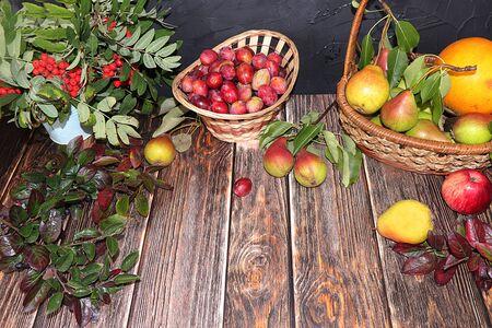 가을 나무 테이블에 뜨거운 차와 디저트 한 잔, 잎이 있는 나무 테이블에 야채와 과일이 있고 평평한 평지, 꼭대기 전망이 있습니다. 추운 가을, 수확과 다가오는 겨울에 집의 아늑함과 편안함