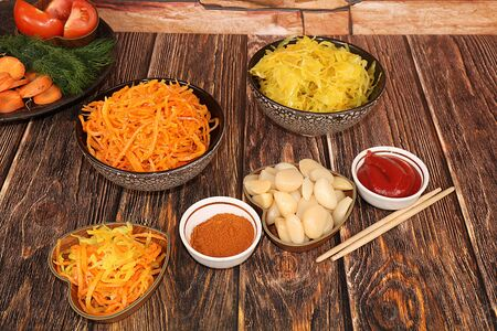 Chinese side dishes for barbecue dinner - kimchi and various kinds of vegetables, a set of fermented foods that are good for intestinal health, carrots, cabbage, garlic, kimchi. top view of glass bowls on wooden background, flat lay, copy space 免版税图像