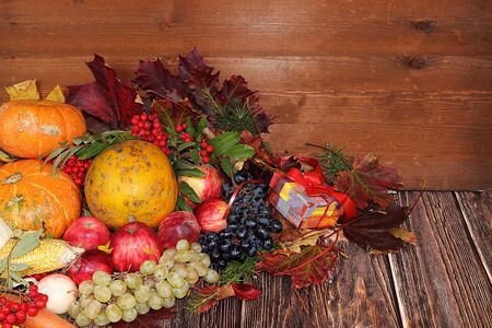 Thanksgiving, autumn background with seasonal autumn nature berries, pumpkins, apples, gifts and leaves on wooden background, copy space. Happy Thanksgiving concept
