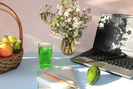 Workplace, Computer, flowers, empty notebook with pen and basket with grapes and apples, lime on a desktop computer sunny table, copy space. A break at work in the office in comfortable conditions, the concept of proper nutrition and a healthy lifestyle