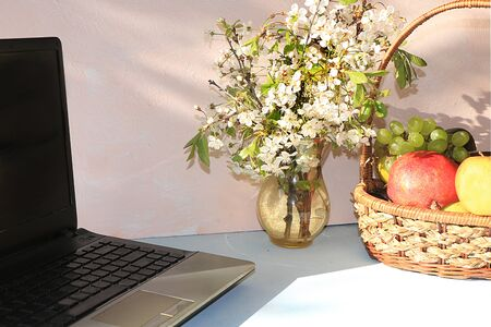 Workplace, Computer, flowers and a basket of grapes and apples on a desktop computer sunny table, copy space. A break at work in the office in comfortable conditions, the concept of proper nutrition and a healthy lifestyle
